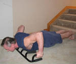The Atlas push up bar using wide grip on the floor